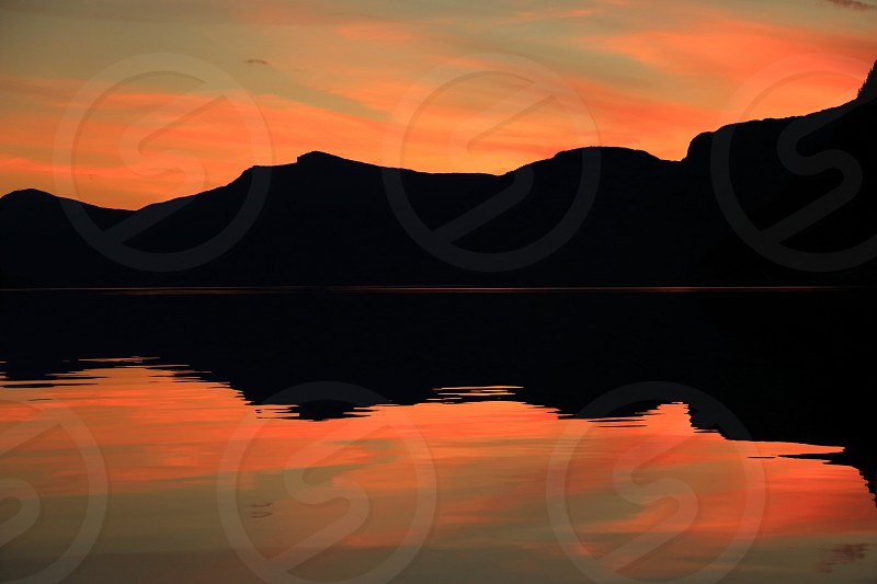 Dramatic sky over mountain silhouette at Norwegian fjord  photo