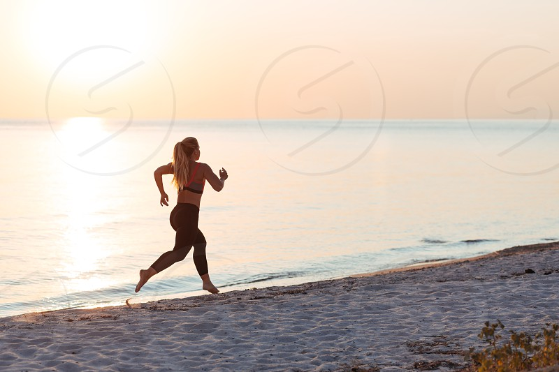 Young woman running on the beach at sunset photo