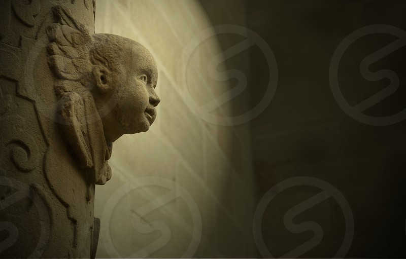 Angel face sculpted in architecture. Stylized photo of an angel. Cherub's head from the profile photo