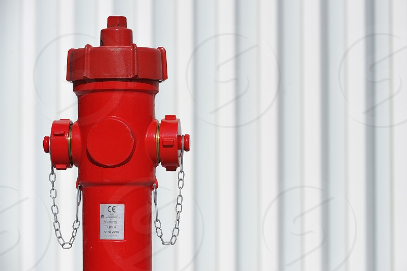 Red hydrant on a white wall photo