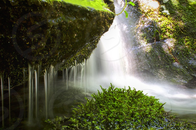 Washing It Away Waterfall near a large boulder with moss and flowing water.  photo