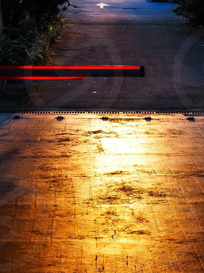 yellow light shining on paved driveway with red bars and white pointing arrow photo