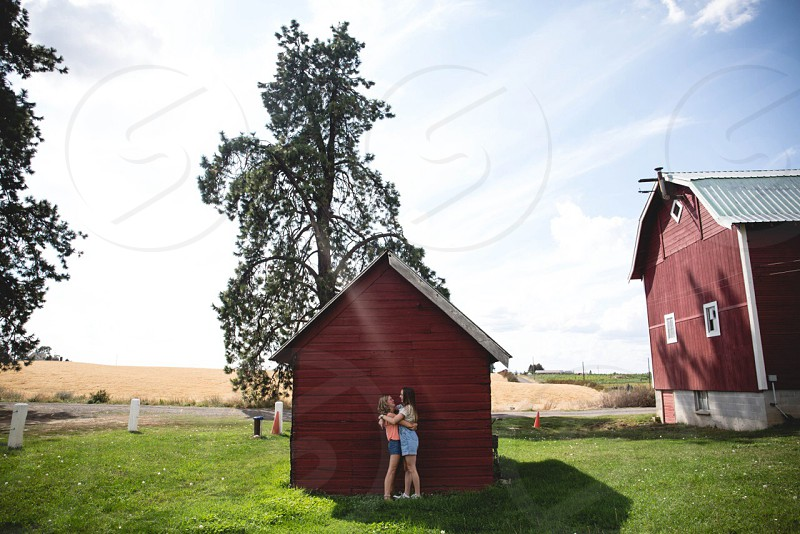 2 women standing near brown wooden barn embracing each other photo