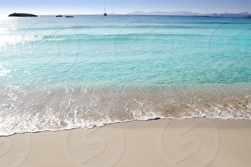 anchor boats in horizon of Illetas beach formentera balearic islands photo