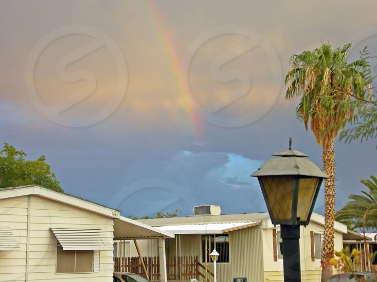 black outdoor lantern white painted house at cloudy sky with rainbow photo
