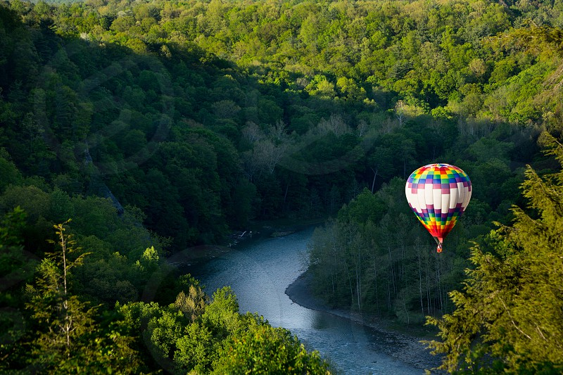 rainbow chevron stripe hot air balloon above river and green forest photo