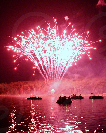Pink fireworks fountain over boats in lake  photo