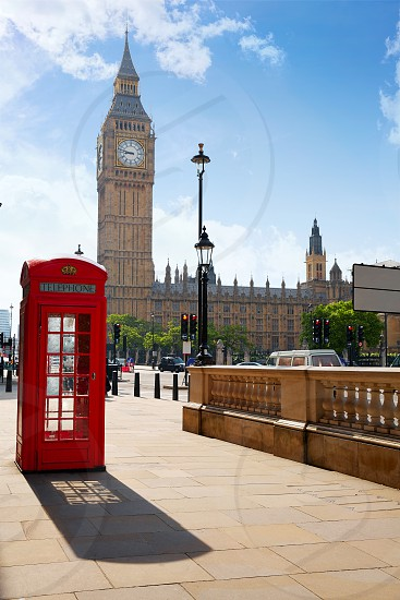 London old red Telephone box and Big Ben clock tower in England photo