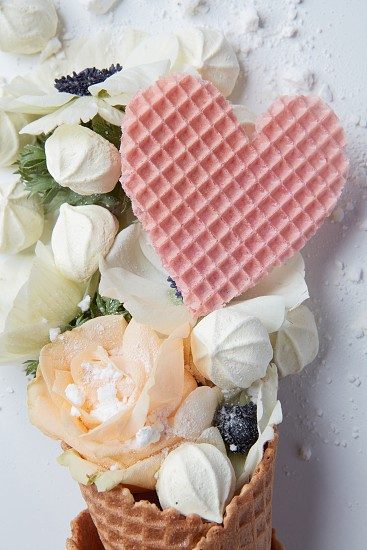 Waffle cone with organ flower and heart on a white background photo