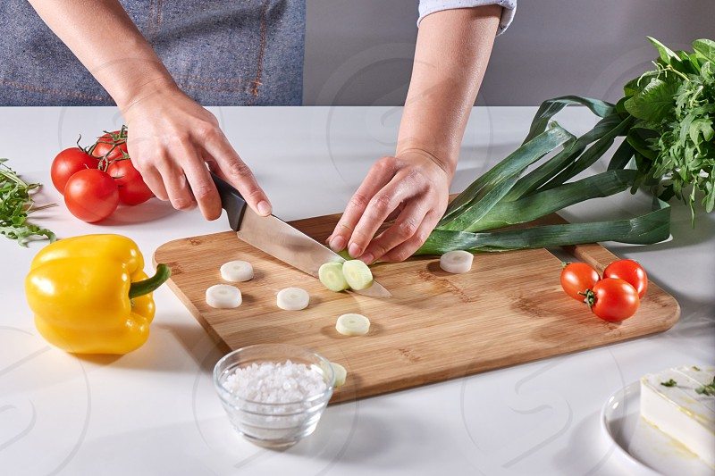 Woman's hands cut green leek on a wooden board on the kitchen table with various fresh vegetables. Step by Step Salad Cooking photo