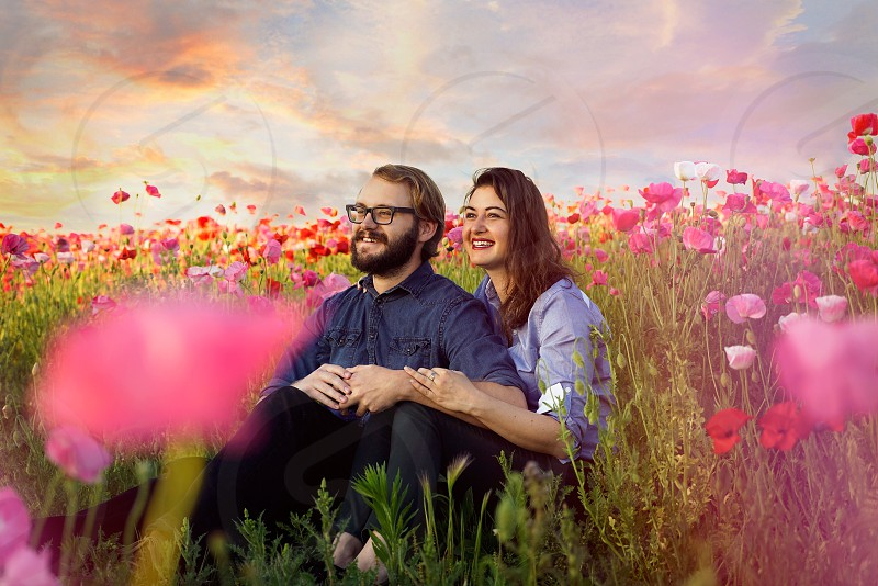 A happy couple sitting in a field while surrounded by pink red and white poppies. photo