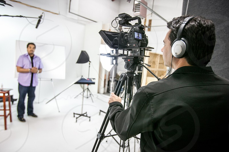 A videographer shoots a project in a studio with a microphone lights camera tripod teleprompter headphones. photo