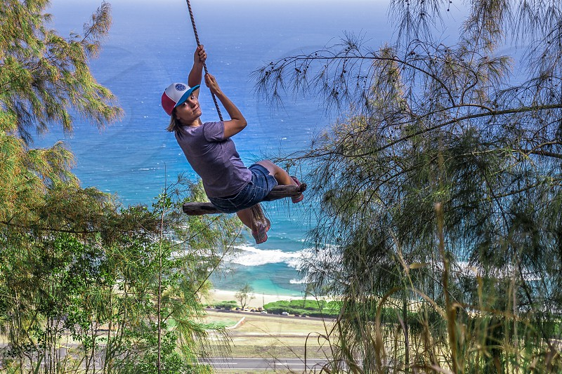 Women swinging on a rope in the forest top of the mountain with ocean view photo