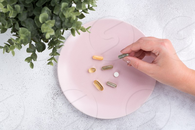 Flat lay of a woman picking up a supplement pill from a pink plate of supplements. photo