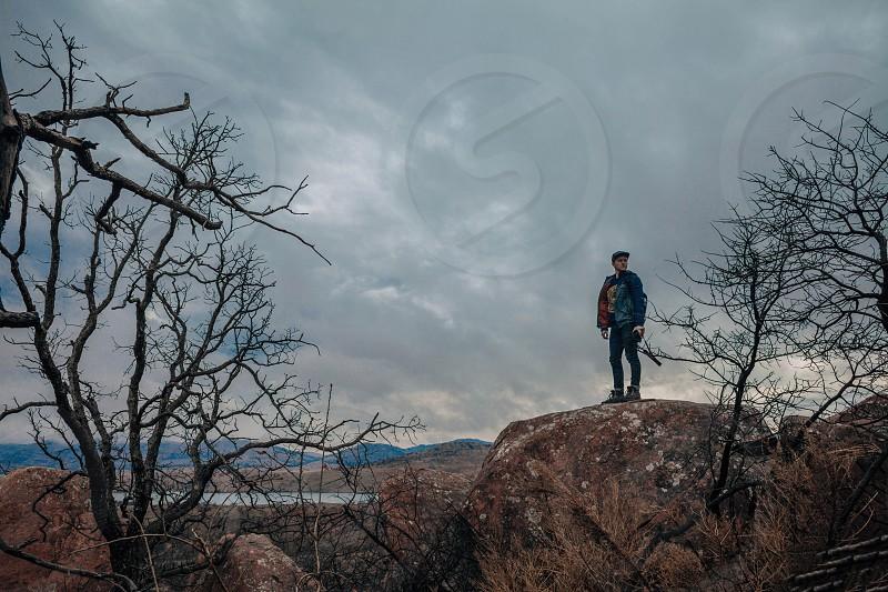 man wearing a black cap standing on a rock photo