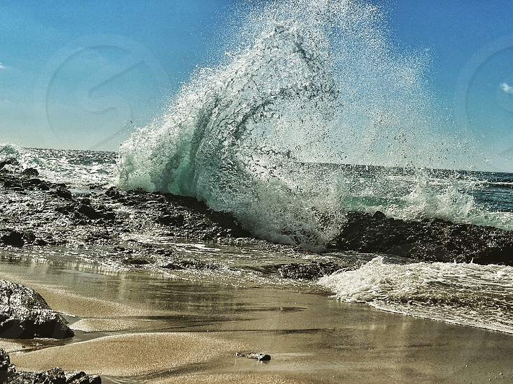 waves hitting rocks under clear sky during daytime photo
