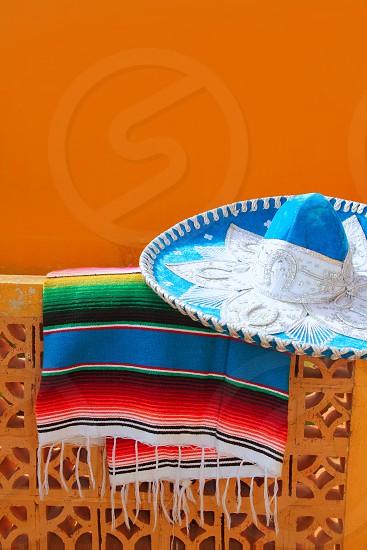 charro mariachi blue mexican hat serape poncho over orange tiles wall photo