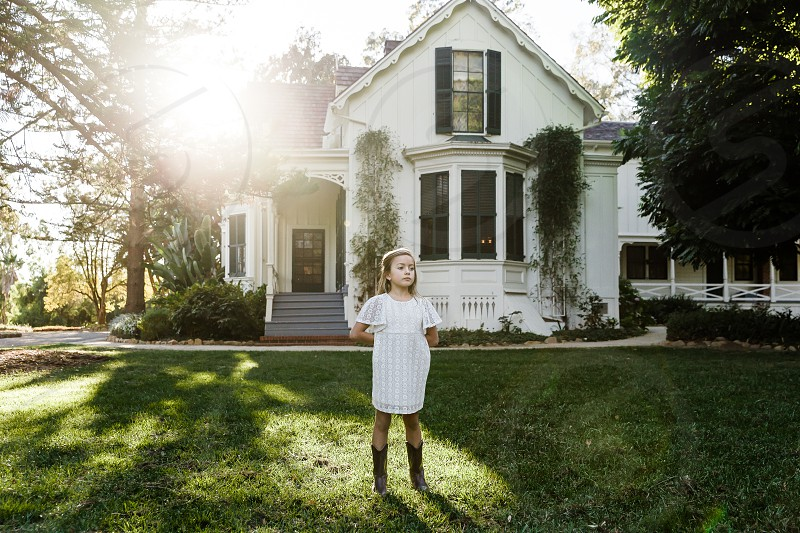 little girl in a white dress and cowgirl boots standing in a yard in front of a white house photo