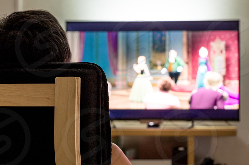 person watching carton movie on black flat screen television photo
