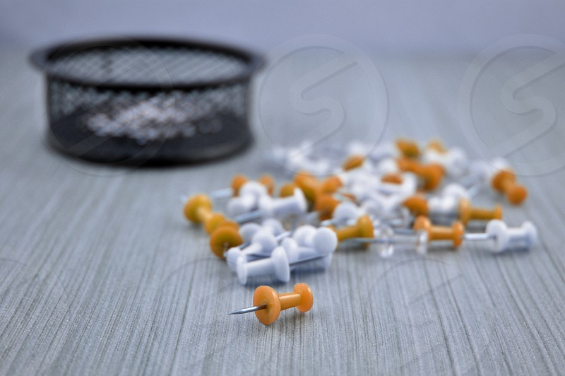 Color pins. Tack on a wooden background. Orange and white plastic tacks. Set of color pins photo