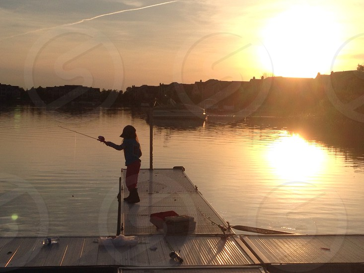 Sunset with little girl fishing photo