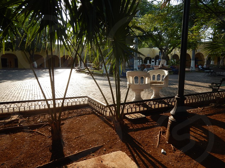 Merida Yucatan Mexico park trees chairs you and me fence photo