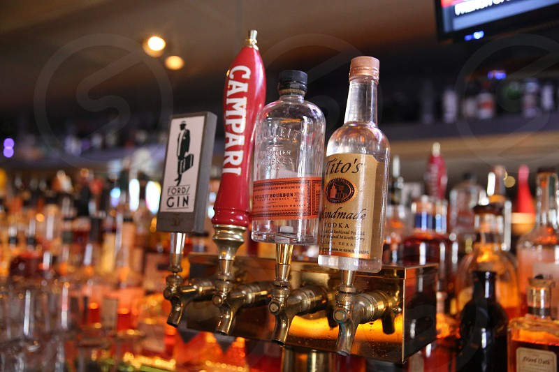 campari bottle beside fordy gin liquor dispenser photo