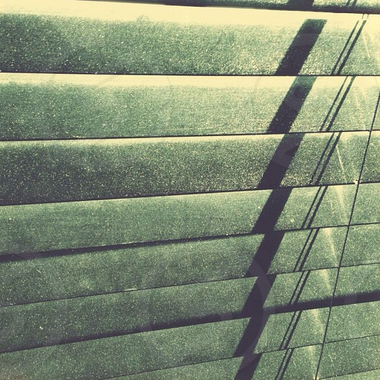 Dusty black blinds with filtered sunlight.  photo