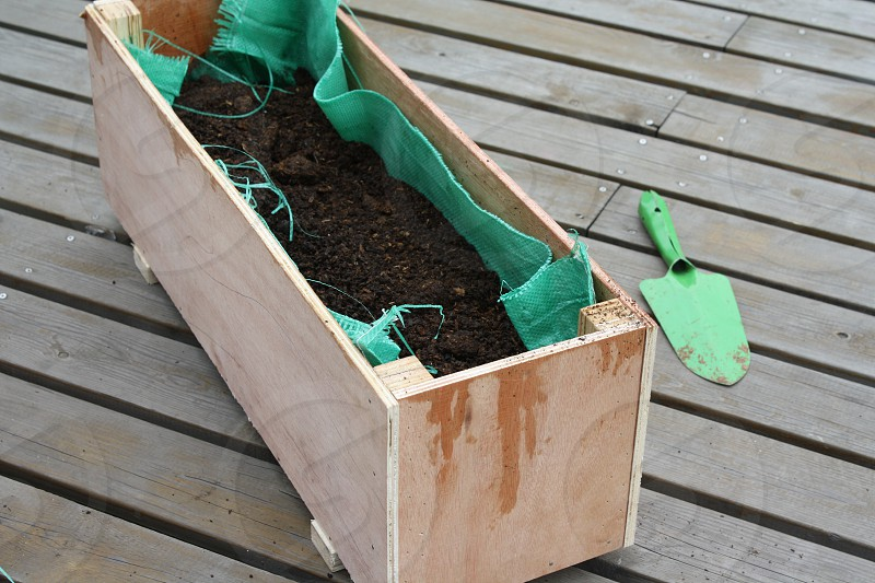Wood planter box with brown dirt inside photo