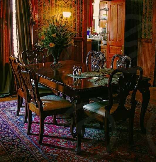 Wood paneled dining room with vintage dining set and an Oriental rug. photo