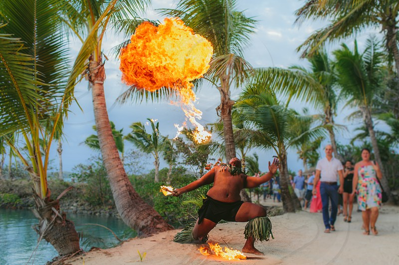 fire fire dancer fire blow yellow tropical entertainment celebration party palm tree torch flame yellow ethnic pacific islander fiji photo