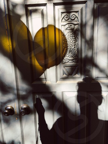 shadow of a man with yellow balloons on white door photo