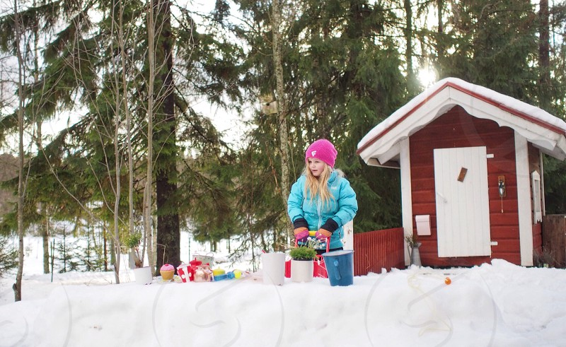 Young girl has brought her toys out in the snow photo
