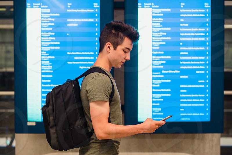 Young man standing in the railway station next to screens with schedule planning a travel travelling with backpack photo