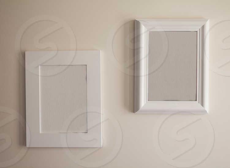 Closeup view on two empty picture frames on white wall. photo