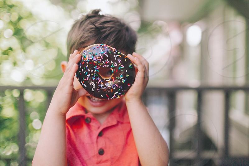 A little boy holding up a donut. photo