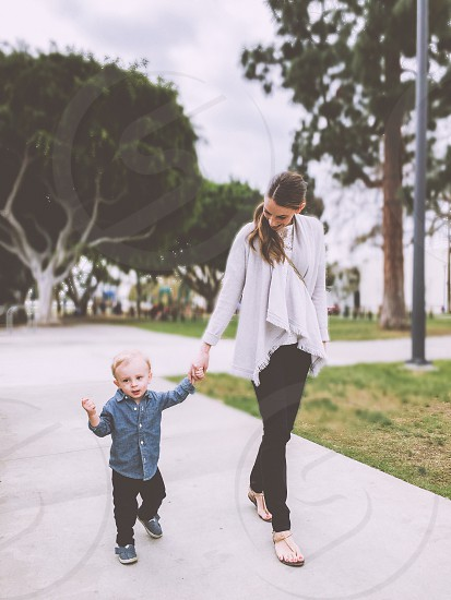 woman in black pants holding boy in blue long sleeved button down shirt and black pants walking at pathway photo