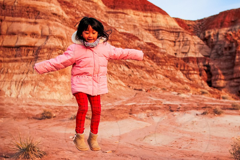 girl in pink jacket and red pants jumping in front of canyon range photo
