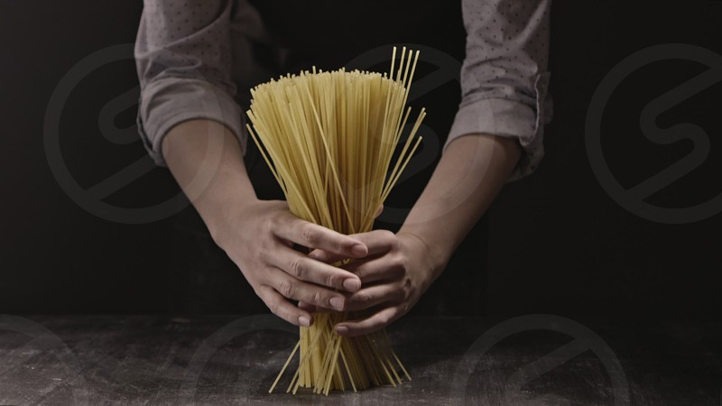 Raw homemade uncooked pasta spaghetti in a woman's hands as a bouquet on a wooden rustic background. Slow motion Full HD video 240fps 1080p. Concept of italian food and cooking dinner. photo