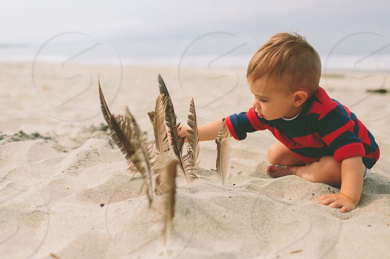 A little boy playing in the sand with feathers.  photo