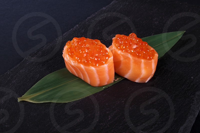 rolls with fish eggs on leaf green black background photo