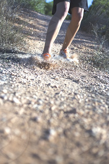 person wearing tennis shoes and black shorts sliding down a gravel hill with grass photo