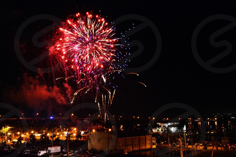 red and blue fireworks display above beige building photo