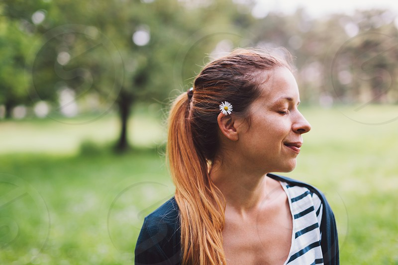 Young woman in nature with a flower in her hair photo