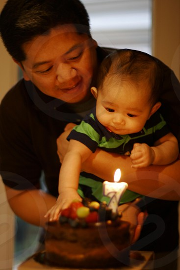 man in black shirt holding a baby front of brown birthday cake photo