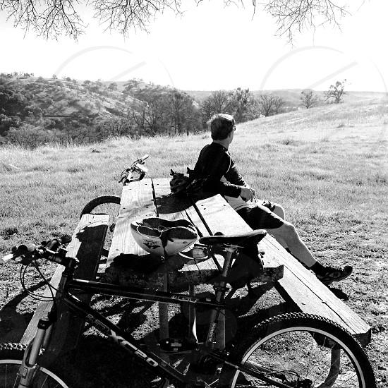 B/W mountain biker taking a break at a picnic table photo