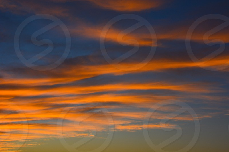 Orange clouds repeating pattern blue sky evening sun glow color photo