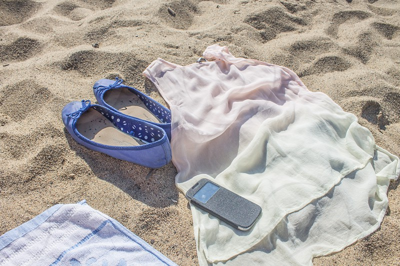 smartphone with gray flip view case placed on white and pink ombre sleeveless dress on white sand photo