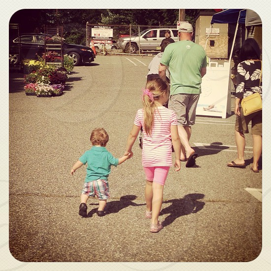girl holding hand of boy while walking photo