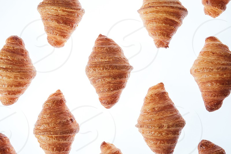 Delicious freshly baked crispy croissants pattern on a light background. Close up. Continental breakfast. photo